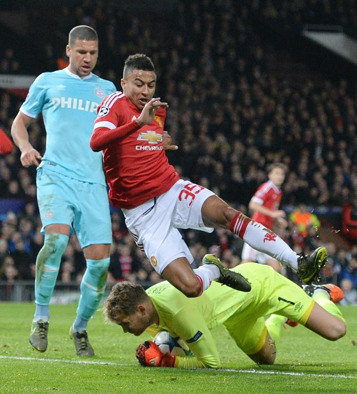 PSV Eindhoven's goalkeeper Jeroen Zoet saves the ball from Manchester United's midfielder Jesse Lingard (Top C) during a UEFA Champions League match at Old Trafford Stadium in Manchester, nort