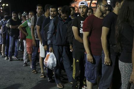 Syrian refugees line up before boarding the passenger ship Eleftherios Venizelos at the port on the Greek island of Kos, August 15, 2015. REUTERS/Alkis Konstantinidis