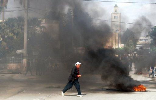 A Tunisian man walks past burning tyres during a demonstration in Kasserine in western Tunisia on October 22, 2012. Tunisia announced that it had arrested 16 men suspected of belonging to a group with ties to Al-Qaeda in the Islamic Maghreb, in the western regions of Kasserine and Jendouba near the Algerian border