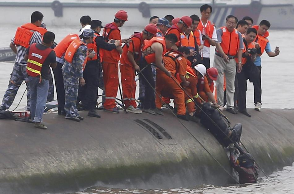 Rescuers help lift a survivor pulled from the capsized cruise ship on the Yangtze River in Jianli in central China's Hubei province Tuesday June 2, 2015. Divers on Tuesday pulled survivors from inside