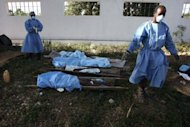"A nurse walks past the bodies of cholera victims at the Ste. Therese hospital in Hinche on November 20, 2010. About 8,000 people have died in the epidemic since October 2010 but UN spokesman Martin Nesirky said a complaint made by lawyers for the victims was ""non-receivable"" under a 1946 convention setting out the UN's immunities for its actions"