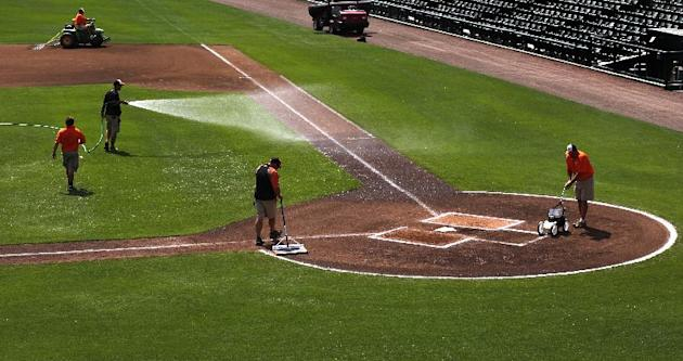 The ground crew at Ed Smith Stadium prepare the field for a Baltimore Orioles intra-squad spring training baseball game in Sarasota, Fla., Sunday, March 1, 2015. Grapefruit League action starts Tuesda