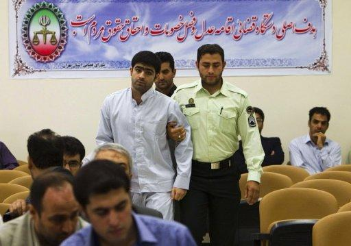 An Iranian policeman leads Majid Jamali Fashi, the man convicted of the assassination of the nuclear scientist Masoud Ali Mohammadi, to his trial at Tehran's Revolutionary Court on August 23, 2011. Iran executed Jamali Fashi on Tuesday