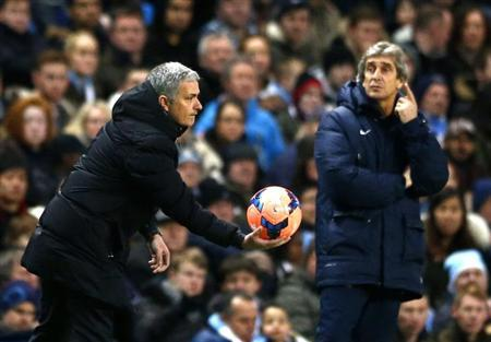 Chelsea manager Jose Mourinho holds the match ball as his Manchester City counterpart Manuel Pellegrini reacts during their English FA Cup fifth round soccer match at the Etihad Stadium in Manchester, northern England February 15, 2014. REUTERS/Darren Staples