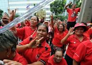 """Thai """"Red Shirt"""" supporters shout sloagans during the terrorism trial of the group's leaders outside the Criminal Court in Bangkok. The terrorism trial of Thai """"Red Shirt"""" leaders in connection with deadly civil unrest in 2010 has been postponed until November because some of the defendants enjoy immunity while parliament is in session"""