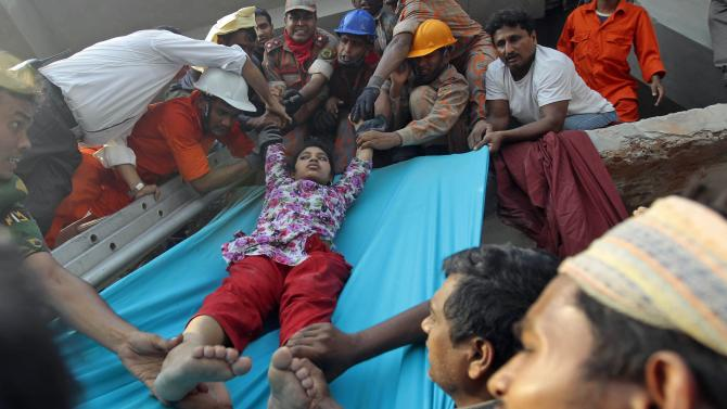 Rescuers lower down a survivor from the debris of a building that collapsed in Savar, near Dhaka, Bangladesh, Wednesday, April 24, 2013. An eight-storey building housing several garment factories collapsed near Bangladesh's capital on Wednesday, killing dozens of people and trapping many more under a jumbled mess of concrete. Rescuers tried to cut through the debris with earthmovers, drilling machines and their bare hands. (AP Photo/A.M.Ahad)