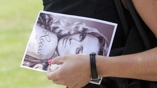 A mourner leaves, holding a picture of model Reeva Steenkamp, after her memorial service at the Victoria Park Crematorium in Port Elizabeth (Reuters)
