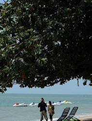 Foreigners are seen enjoying an afternoon at Ferringhi beach near George Town on Penang resort island in Malaysia, on August 26, 2010. With its warm climate, political stability and modern economy, Malaysia has drawn 19,488 foreigners to settle in the country since launching the Malaysia My Second Home (MM2H) programme 10 years ago