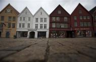 People walk near Bryggen (the Wharf) near the marina in downtown Bergen in this March 20, 2012 file photo. REUTERS/Stoyan Nenov/Files