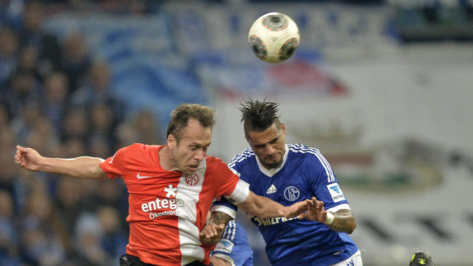 Mainz's Nikolce Noveski, left, and Schalke's Kevin-Prince Boateng, right, challenge for the ball during the German Bundesliga soccer match between FC Schalke 04 and FSV Mainz 05 in Gelsenkirchen,  Germany, Friday, Feb. 21, 2014