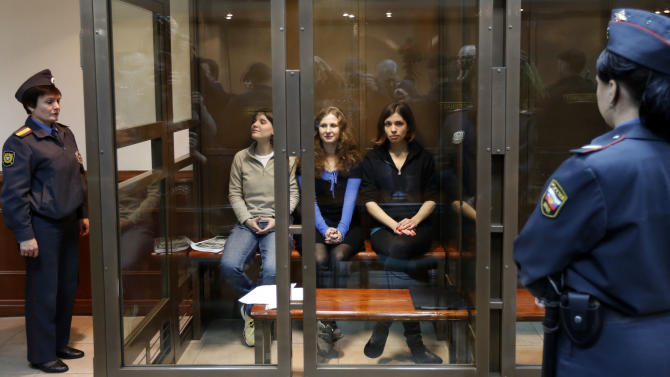 Feminist punk group Pussy Riot members, from left, Maria Alekhina, Yekaterina Samutsevich and Nadezhda Tolokonnikova sit in a glass cage at a court room in Moscow, Wednesday. Oct. 10, 2012. Three members of the punk band Pussy Riot are set to make their case before a Russian appeals court that they should not be imprisoned for their irreverent protest against President Vladimir Putin. Their impromptu performance inside Moscow's main cathedral in February came shortly before Putin was elected to a third term. The three women were convicted in August of hooliganism motivated by religious hatred and sentenced to two years in prison. (AP Photo/Sergey Ponomarev)