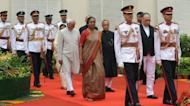 India's new President Pranab Mukherjee (4R) is escorted by presidential bodyguards and parliamentary Speaker Miera Kumar (C) and Vice President of India Hamed Ansari (5L) as he arrives for his swearing-in ceremony at parliament in New Delhi on July 25, 2012