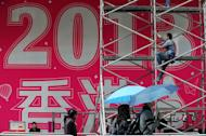 A worker prepares a promotional 2013 banner outside a shopping mall in Hong Kong on Saturday. As the clock strikes 12 on Monday, millions will pop champagne corks and light fireworks while others indulge in quirkier New Year's rituals like melting lead, leaping off chairs or gobbling grapes