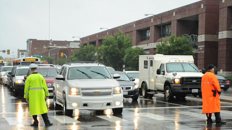 Police officers direct traffic next to the Stuart C. Siegel Center at Virginia Commonwealth University in Richmond, Va. Friday, June 7, 2013. Tropical Storm Andrea doused the area with ample rainfall as the arena hosted graduations for local high schools. (AP Photo/The Progress-Index, Patrick Kane)