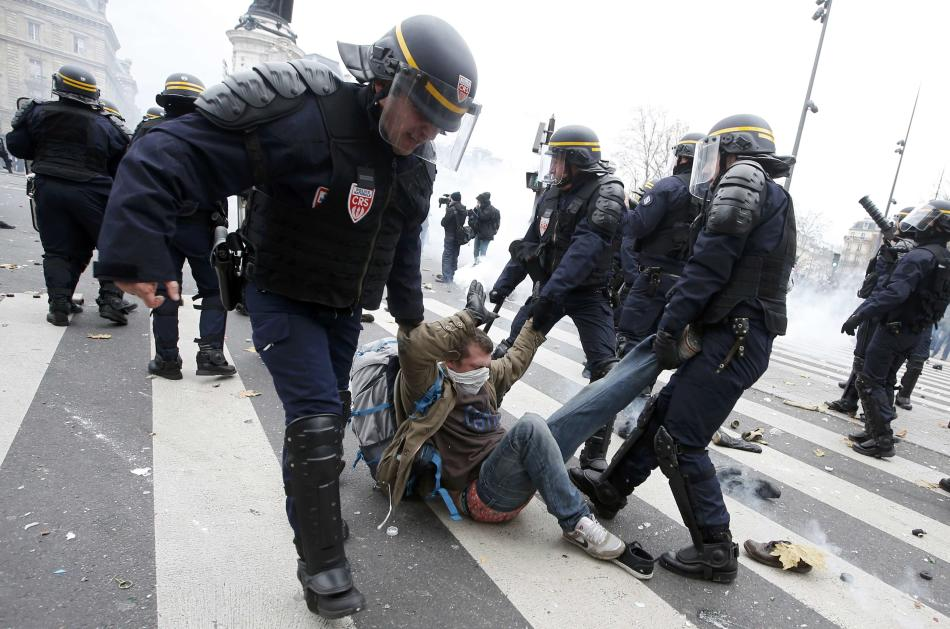 French CRS riot police apprehend a demonstrator during clashes near the Place de la Republique after the cancellation of a planned climate march  ahead of the World Climate Change Conference 2015 in P