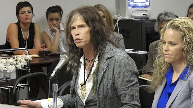 Aerosmith lead singer Steven Tyler testifies on celebrity privacy during a hearing at the Hawaii Capitol in Honolulu on Friday, Feb. 8, 2013. Rock legends Steven Tyler and Mick Fleetwood convinced a Hawaii Senate committee on Friday to approve a bill to protect celebrities or anyone else from intrusive paparazzi. The state Senate Judiciary Committee approved the so-called Steven Tyler Act after the stars testified. The bill would give people power to sue others who take photos or video of their private lives in an offensive way. (AP Photo/Oskar Garcia)