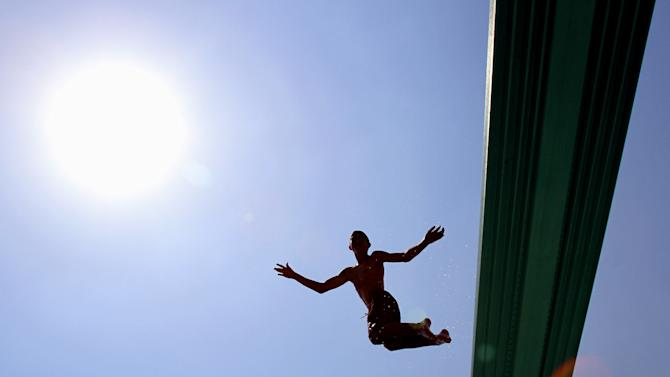 Jake Wenz, 12, jumps off the high board at Centennial Beach in Naperville, Ill.  on Friday July 6, 2012.  There's been no relief day or night from a scorching heat wave in the central U.S., and the deadly temperatures were heading east Friday after Midwest cities like Chicago, St. Louis and Milwaukee set record highs.(AP Photo/Daily Herald,Bev Horne )