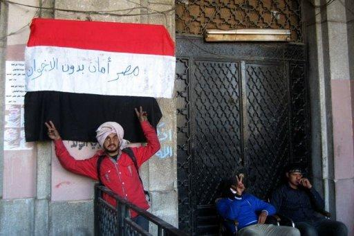 """An Egyptian protester flashes the sign of victory in front a national flag on which is written in Arabic """"Egypt is moor safe without Muslim Brotherhoods'' in front of the Mugamma, Cairo's main administrative building on February 24, 2013. In Cairo on Sunday, protesters blocked the doors to the main administrative building as part of a growing campaign of civil disobedience around the country"""