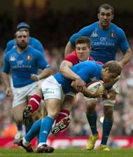 Italy's fly-half Kristopher Burton (2nd R) is tackled by Wales centre Jamie Roberts (3rd R) during their Six Nations rugby union match at the Millennium Stadium in Cardiff, Wales. Wales won 24-3