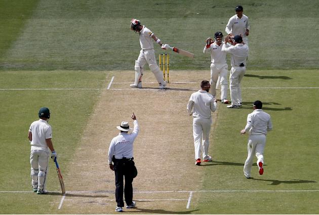 New Zealand's Mark Craig celebrates with team mates as Australia's captain Steve Smith reacts after being dismissed for 53 runs during the second day of the third cricket test match at the Ade