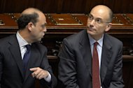 Italy's Interior Minister Angelino Alfano (left) chats with Prime Minister Enrico Letta during a parliamentary session in Rome, on April 29, 2013. Letta said his coalition government would act fast to reverse an austerity policy he argued was killing Italy and called on Europe to become a motor for growth
