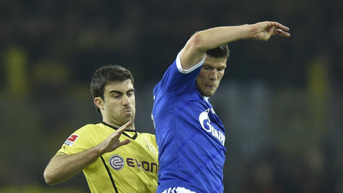 Schalke's Klaas-Jan Huntelaar of the Netherlands, right, and Dortmund's Sokratis of Greece challenge for the ball during  the German Bundesliga soccer match between Borussia Dortmund and FC Schalke 04 in Dortmund,  Germany, Tuesday, March 25, 2014