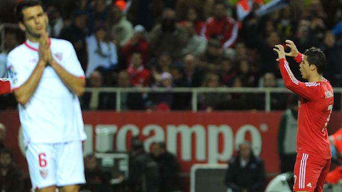 Real Madrid's Portuguese forward Cristiano Ronaldo (R) celebrates after scoring during their Spanish league football match Sevilla FC vs Real Madrid on December 17, 2011 at Ramon Sanchez Pizjuan stadium in Sevilla. Real Madrid won 6-2.    AFP PHOTO/ JORGE GUERRERO (Photo credit should read Jorge Guerrero/AFP/Getty Images)