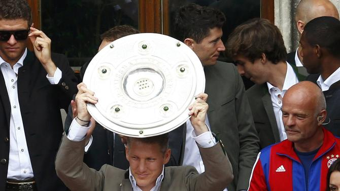 Bayern Munich's player Schweinsteiger holds the trophy as he celebrates with his teammates winning the German Bundesliga title in front of the town hall, in downtown Munich