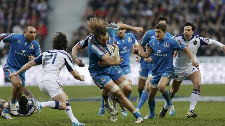 Italy's Joshua Furno runs with the ball as France's Maxime Machenaud looks on during their Six Nations rugby union match at the Stade de France in Saint-Denis