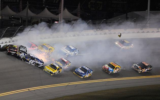 Jeff Gordon, left, slides into the wall as he wrecks with Kurt Busch, second from left, Jimmie Johnson (48) and other drivers during the NASCAR Budweiser Shootout auto race at Daytona International Sp