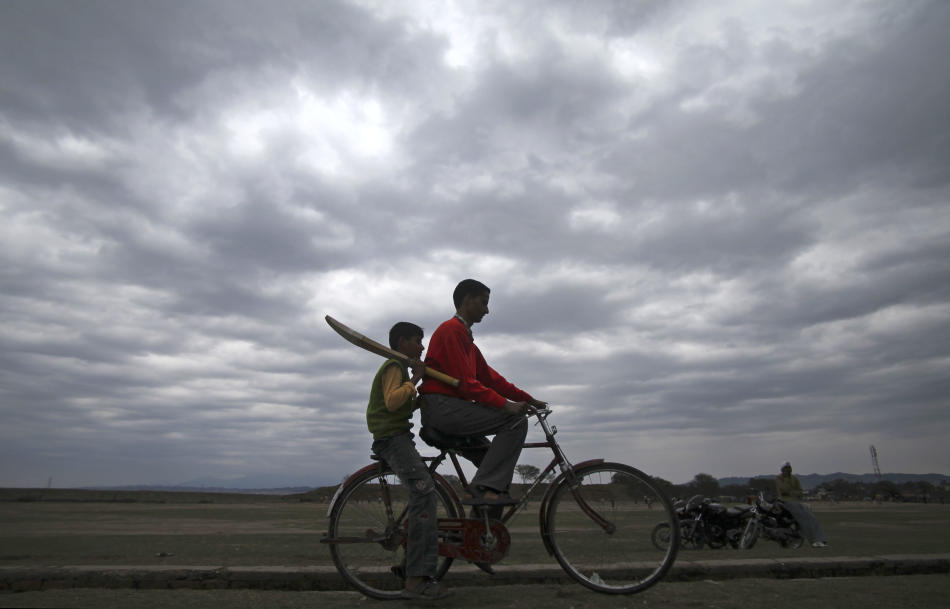 In this Sunday, Feb. 13, 2011 photo, a boy holds a cricket bat and rides a bicycle on the outskirts of Jammu, India. The international cricket landscape has changed dramatically, with India now the co