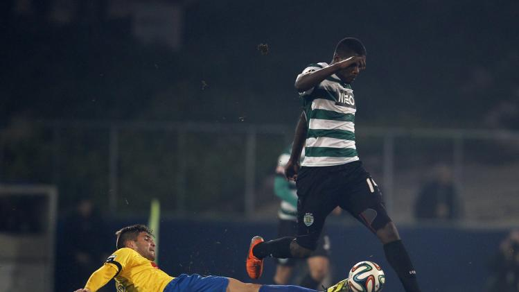 Sporting's William Carvalho is tackled by Estoril's Joao Pedro during their Portuguese Premier League soccer match at the Coimbra da Mota stadium in Estoril