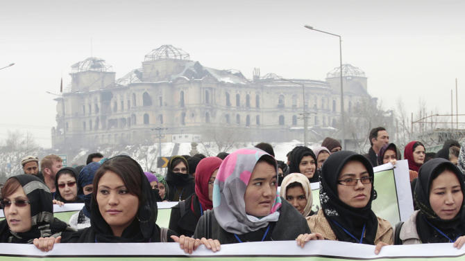 Afghan women carry a banner during a march calling for end of violence against women, in Kabul, with the Darul Aman palace seen in the background, Afghanistan, Thursday, Feb. 14, 2013. Dozens of Afghan activists have marked Valentine's Day by marching in Kabul to denounce violence against women. Concern has risen after rights organizations last year found that Afghan women are frequently victims of violence — despite a law against it and increased prosecution of abusers. (AP Photo/Musadeq Sadeq)