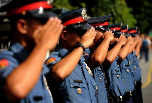 Philippine police officers salute as they stand at attention at the Philippine National Police headquarters in suburban Manila in 2011. Philippine authorities have ordered the arrest of ten policemen accused of kidnapping four South Korean tourists in a plot involving their countrymen tour guides, the Manila City government said Monday