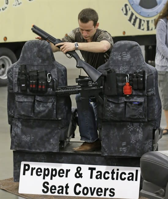 """Niel Burnett, of Covers & Camo, demonstrates a seat cover during the PrepperCon expo Friday, April 24, 2015, in Sandy, Utah. Hundreds of survivalists and """"preppers"""" are gathering in the Salt"""