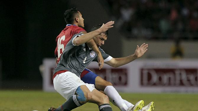 Deiver Vega of Costa Rica fights for the ball with Pablo Aguilar of Paraguay during their international friendly soccer match at the National Stadium in San Jose