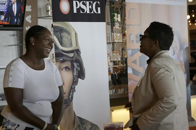 In this photo taken Tuesday, June 30, 2015, Sophia Lewis, left, with PSEG Long Island, speaks to an attendee about employment opportunities during a job fair at Citi Field in New York. U.S. employers