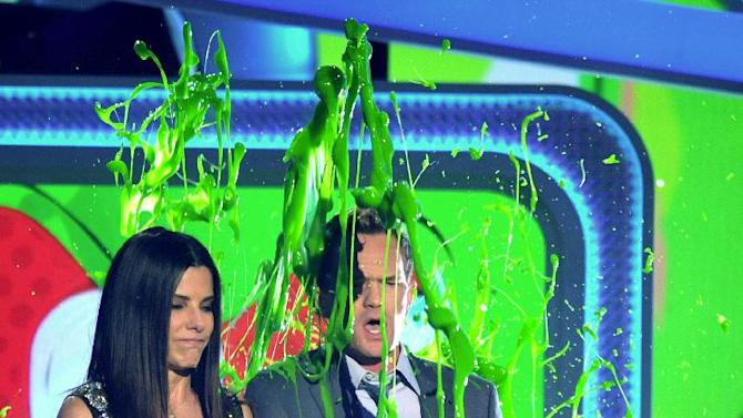 Sandra Bullock and Neil Patrick Harris get slimed as they present the award for favorite movie actress at the 26th annual Nickelodeon's Kids' Choice Awards on Saturday, March 23, 2013, in Los Angeles. (Photo by John Shearer/Invision/AP)
