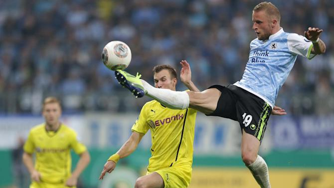 Munich's Daniel Adlung, right, and Dortmund's Kevin Grosskreutz challenge for the ball during the German soccer cup second round match between TSV 1860 Munich and Borussia Dortmund, in Munich, southern Germany, Tuesday, Sept. 24, 2013