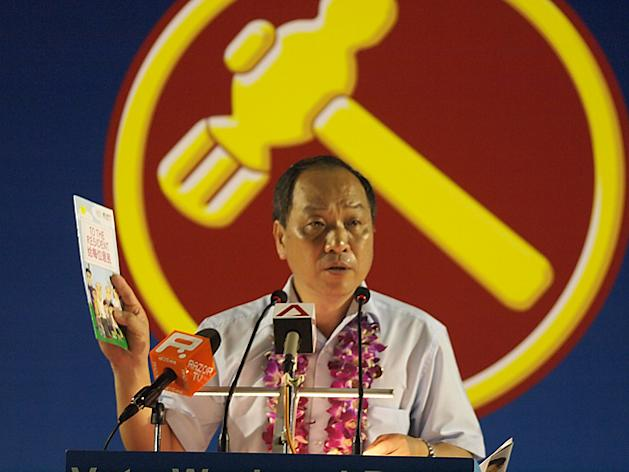 """WP chief Low Thia Khiang holds up another copy of the PAP manifesto that was distributed to Hougang residents, saying, """"I've told the PAP it's not their money — it is the country's money, and Lee Kuan Yew admitted before that the government's money is the people's money,"""" (Yahoo! photo/Jason Ong)"""