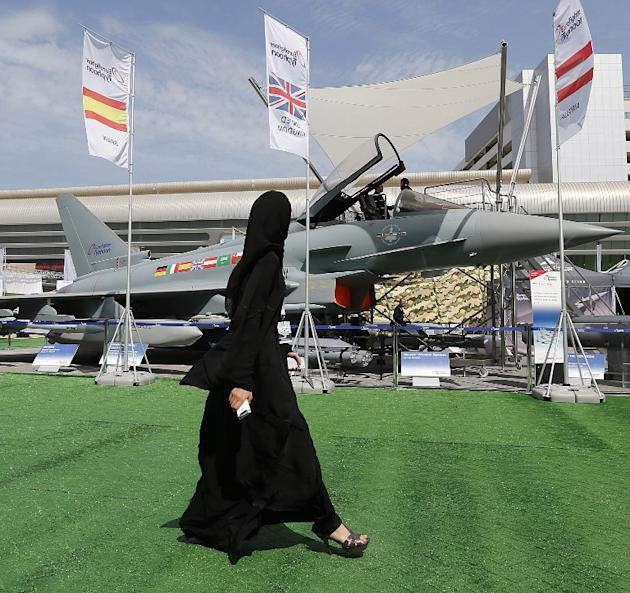 A woman walks past a Eurofighter Typhoon aircraft on display at a military show launching the International Defence Exhibition and Conference (IDEX) at the Abu Dhabi National Exhibition Centre in the