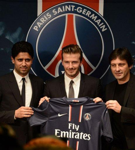 David Beckham (C) poses with his new jersey at the Parc des Princes stadium in Paris, on January 31, 2013