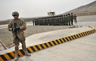 A US soldier stands guard as Afghanistan's Public Protection Forces (APPF) soldiers stand to attention on a base on the outskirts of Kabul on March 15, 2012. Teh US is seeking to ensure any remaining soldiers in Afghanistan will have immunity from prosecution in local courts