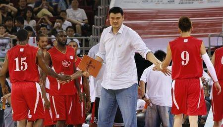 Retired Chinese and NBA basketball star Yao Ming encourages his NBA All-star team during a charity basketball match against the Chinese national team in Beijing