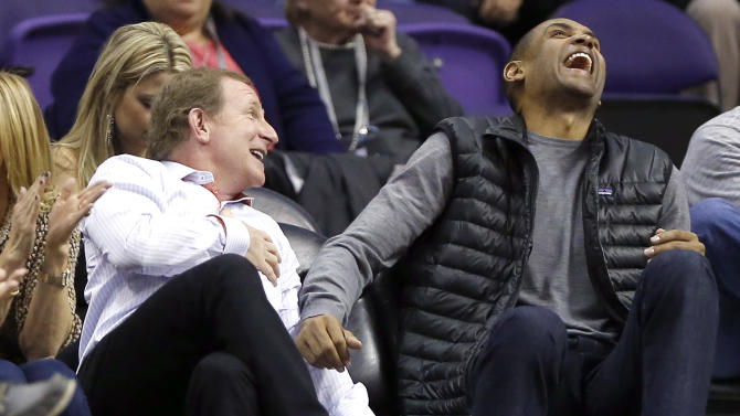 Phoenix Suns owner Robert Sarver, left, laughs with retired NBA player Grant Hill during the second half of an NBA basketball game between the Portland Trail Blazers and the Phoenix Suns, Wednesday, Nov. 27, 2013, in Phoenix