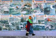 A woman walks past a row of posters Gannan Tibetan Autonomous Prefecture in western China's Gansu province in 2005. A 26-year-old woman immolated herself Tuesday in a Tibetan-populated region of northwest China after chanting slogans calling for the return of the Dalai Lama, the Free Tibet campaign group said
