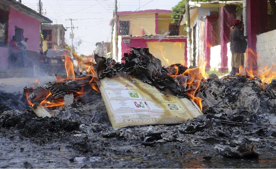 Burning electoral materials are seen outside a polling station vandalised by members of the teacher's union CNTE in Juchitan
