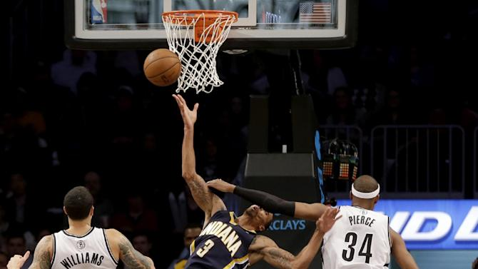 Brooklyn Nets' Paul Pierce, right, commits a flagrant foul against Indiana Pacers' George Hill, center, while Deron Williams watches during the second half of an NBA basketball game Monday, Dec. 23, 2013 in New York. Pierce was ejected from the game. The Pacers defeated the Nets 103-86