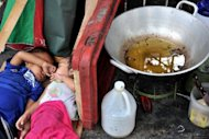 Homeless children sleep beside a frying pan at a street in Manila in January 2012. The Philippine government on Tuesday proposed a budget hike for next year of more than 10 percent, making it worth $47.8 billion, as it seeks to fight poverty and boost social services
