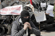 A masked pro-Russian activist guards a barricade at the regional administration building that they had seized earlier in Donetsk, Ukraine, Tuesday , April 15, 2014. Several government buildings have fallen to mobs of Moscow loyalists in recent days as unrest spreads across the east of the country. (AP Photo/Efrem Lukatsky)